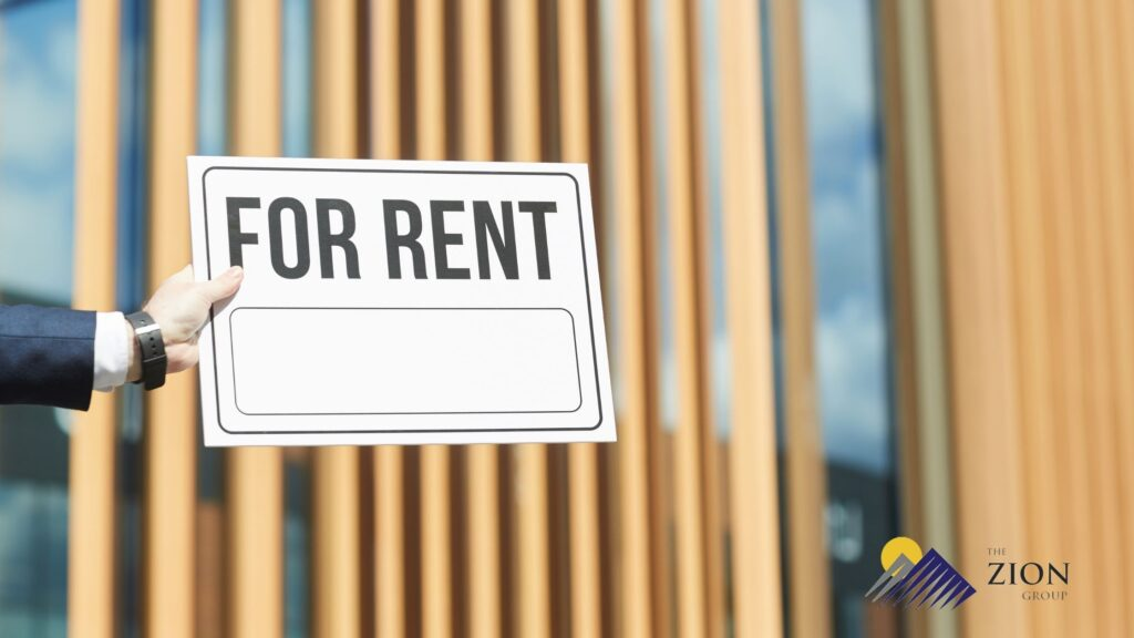 A businessman holding a for rent sign in front of a commercial building